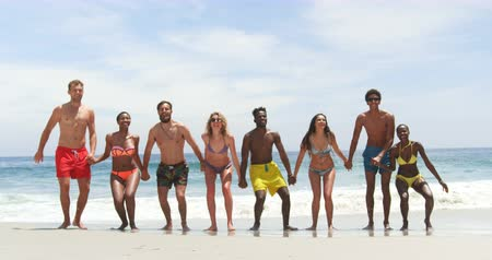 socialization : Front view of mixed-race friends jumping together on the beach. They are holding hands of each other 4k