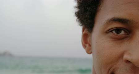 o : Close-up of African American man standing on the beach. He is smiling and looking at camera 4k