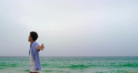 растягивается : Rear view of African american man standing with arms outstretched on the beach. He is looking at sea 4k
