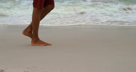 section : Low section of man walking barefoot at beach on a sunny day. Sea waves in the background 4k