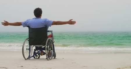 растягивается : Rear view of African American man sitting with arms outstretched on wheelchair with arms outstretched at beach. He is looking at sea 4k