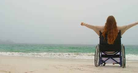растягивается : Side view of young Caucasian woman sitting with arms outstretched on wheelchair at beach. She is feeling blissful 4k