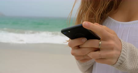 tárcsázás : Mid section of woman using mobile phone on the beach. Sea waves in the background 4k
