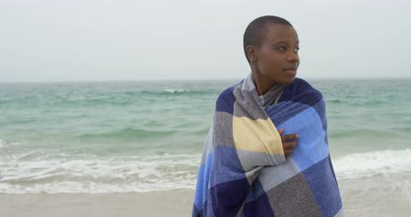 serenidade : Front view of African american woman wrapped in blanket on the beach. She is smiling and looking away 4k