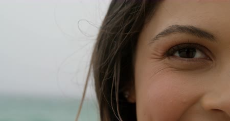 sní : Close-up of Caucasian woman standing on the beach. She is smiling and looking at camera 4k Dostupné videozáznamy