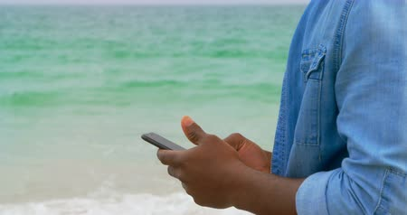 tárcsázás : Side view of African American man using mobile phone on the beach. He is standing on the beach 4k Stock mozgókép