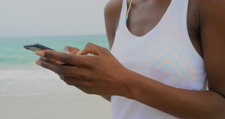 tárcsázás : Front view of African American woman using mobile phone on the beach. She is smiling 4k Stock mozgókép