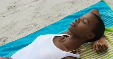kapalı : High angle view of African american woman sleeping on the beach. She is asleep 4k Stok Video