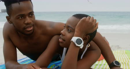 支出 : Front view of African american couple relaxing on the beach. They are spending time together 4k