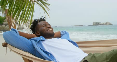 fele olyan hosszú : Front view of African american man relaxing in a hammock on the beach. He is smiling and looking away 4k