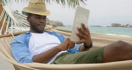 raszta : Front view of African american man using digital tablet on the beach. He is relaxing in a hammock 4k
