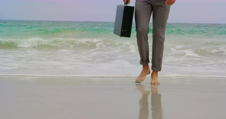 boso : Low section of Businessman walking barefoot with briefcase on the beach. Sea waves in the background 4k