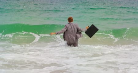 aktatáska : Rear view of Caucasian Businessman walking with briefcase in the sea at beach. He is playing with sea waves 4k