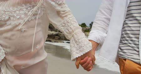 mid section : Mid section of couple walking hand in hand on the beach 4k. They are spending time together 4k
