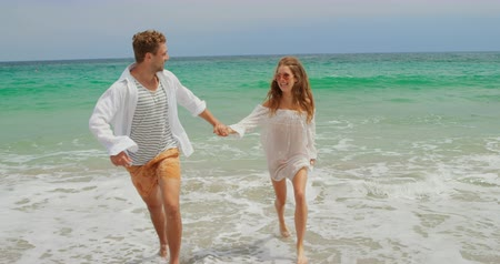 teljes hosszúságú : Front view of Caucasian couple running on the beach. They are having fun 4k