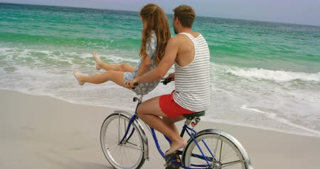 teljes hosszúságú : Side view of Caucasian couple riding a bicycle on the beach. They are spending time together 4k