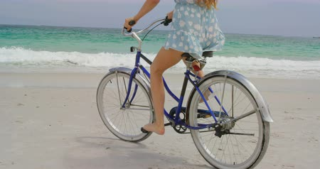 vest : Low section of woman riding a bicycle on the beach. Sea wave in the background 4k