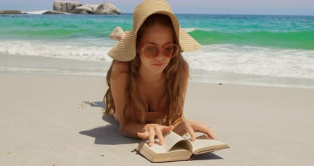teljes hosszúságú : Front view of Caucasian woman in hat reading book on the beach. She is relaxing on the beach 4k