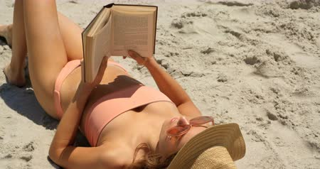 livros : High angle view of Caucasian woman in hat reading a book on the beach. She is relaxing on the beach 4k