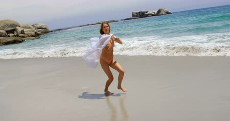 teljes hosszúságú : Side view of Caucasian woman running with sarong on the beach. She is having fun 4k