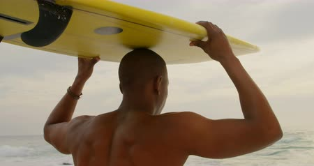 уик энд : Rear view of African American male surfer carrying surfboard on his head at beach. He is walking on the beach 4k Стоковые видеозаписи