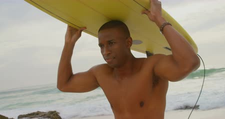 определение : Front view of African American male surfer carrying surfboard on his head at beach. He is running on the beach 4k Стоковые видеозаписи