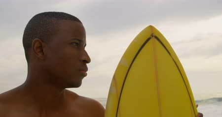 голова и плечи : Front view of African American male surfer standing with surfboard on the beach. He is looking away 4k
