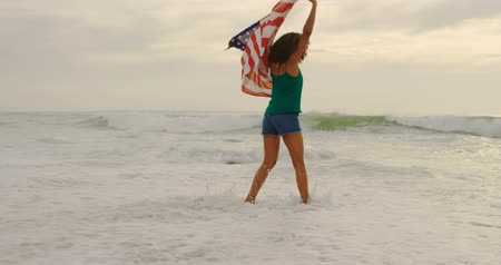 ультра : Front view of African American woman with waving American flag dancing on the beach. She is having fun 4k