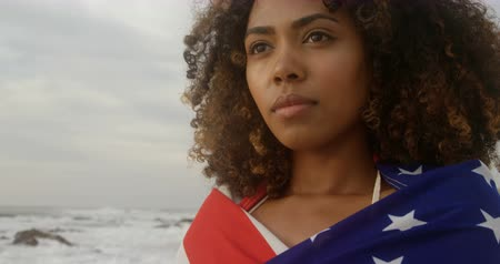 определение : Front view of African American woman wrapped in American flag standing on the beach. 4k Стоковые видеозаписи