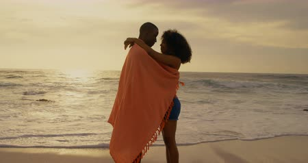 envolto : Side view of African American couple wrapped in blanket on the beach. They are embracing each other 4k