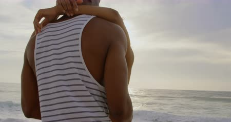 жилет : Side view of African American couple dancing together on the beach. They are spending time together 4k