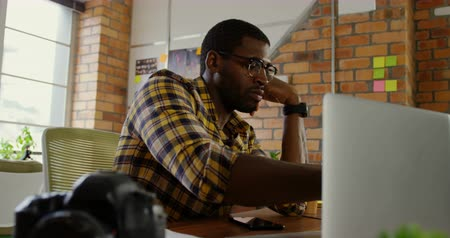 fele olyan hosszú : Front view of African american male graphic designer working at desk in a modern office. He is looking at photographs and administrative paper. 4k Stock mozgókép