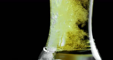 bira fabrikası : Close-up of beer poured in glass against black background. Bubbles and foam in beer glass. 4k