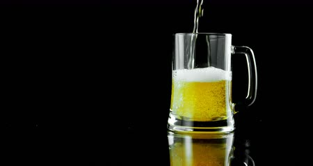 felüdítés : Beer poured in beer mug against black background. Bubbles and foam in beer mug. 4k