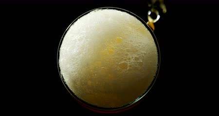 bira fabrikası : High angle view of beer poured in glass against black background. Bubbles and foam forming in glass. 4k Stok Video