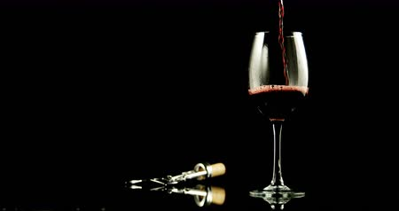 abridor : Close-up of red wine poured in wine glass against black background. Wing corkscrew beside wine glass. 4k Stock Footage