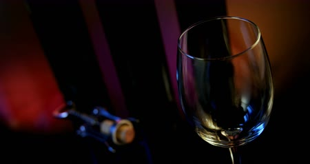 abridor : Close-up of red wine poured in wine glass. Wing corkscrew beside wine glass. 4k Stock Footage