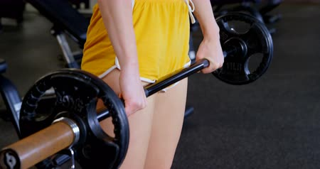 dedizione : Side view of Caucasian woman exercising with barbell in a fitness studio. She is doing squats. 4k