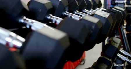 yokluk : Close-up of dumbbells on a rack in fitness studio. Dumbbells arranged in a row 4k