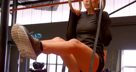 teljes hosszúságú : Front view of beautiful Caucasian woman exercising with gymnastic rings in fitness studio. She is determined and focused. 4k Stock mozgókép