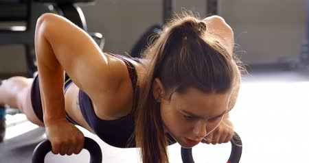 pus : Front view of beautiful Caucasian woman doing push-ups in fitness studio. She is determined and focused. 4k