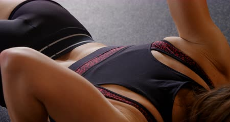 teljes hosszúságú : Rear view of Caucasian woman doing push-ups in fitness studio. She is determined and focused. 4k