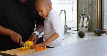 capsicum : Side view of African American father and son cutting bell pepper in kitchen at home. They are preparing food. 4k