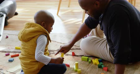 teljes hosszúságú : Side view of African american father and son playing with building blocks in a comfortable home. They are sitting on the floor. 4k