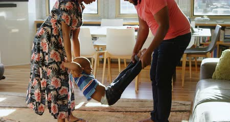 autentico : Side view of African american parents swinging their son in a comfortable home. They are smiling and having fun. 4k