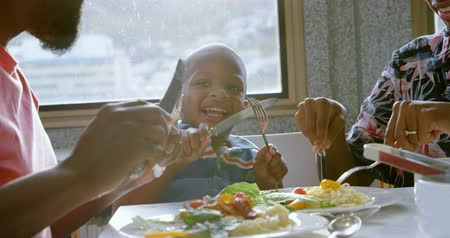 cabeza calva : Front view of smiling African american family having food at dining table in a comfortable home. 4k