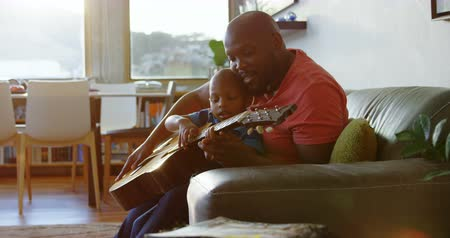 ailelerin : Side view of African american father teaching his son how to play guitar at home. They are sitting on the sofa. 4k Stok Video