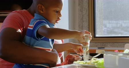 высокой четкости : Side view of African american father and son having food at dining table in home. Son putting salt on salad. 4k Стоковые видеозаписи