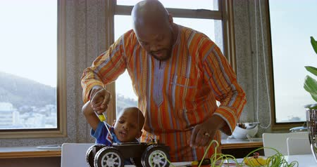 etnia africano : Front view of African american father and son repairing toy car in a comfortable home. They are using screw driver. 4k Stock Footage