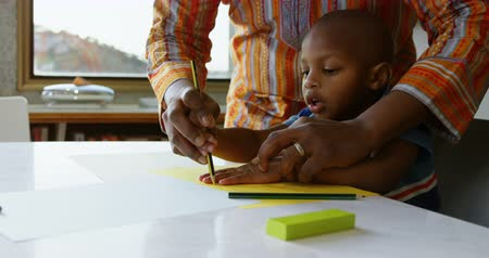 borracha : Front view of African american father and son drawing sketch on a paper on table at home. Father teaching his son 4k